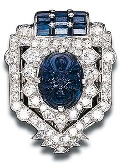 AN ART DECO SAPPHIRE AND DIAMOND CLIP BROOCH, BY CARTIER. Designed as a circular-cut diamond stylised shield-shaped panel set with a central carved cabochon sapphire to the calibré-cut sapphire terminal, circa 1925. Signed Cartier, numbered.
