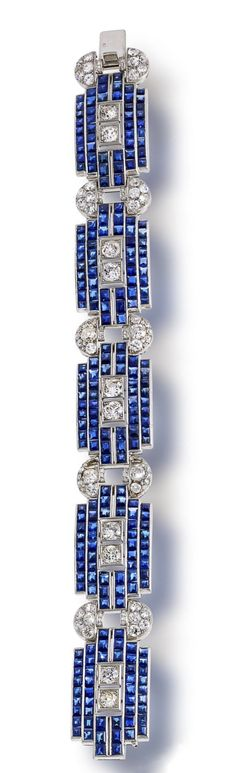 A sapphire and diamond bracelet, circa 1935 composed of geometric links set with calibré-cut sapphires, joined by old European and old mine-cut diamond half-moon shaped links; estimated total sapphire weight: 28.00 carats; estimated total diamond weight: 6.25 carats; mounted in platinum; length: 7 1/2in.