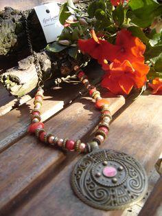 Collar con accesorios rojos y naranja. Medallón labrado en bronce