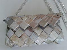 Pochette realizzata con strisce di carta di una rivista di abiti da sposa plastificate e intrecciate. Tracolla in metallo.