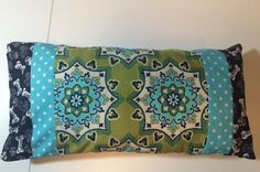 This pillow is made of 100% cotton with a cotton batting lining. It measure 14 x 6 inches and is a small dog pillow. It is handmade and pieced and