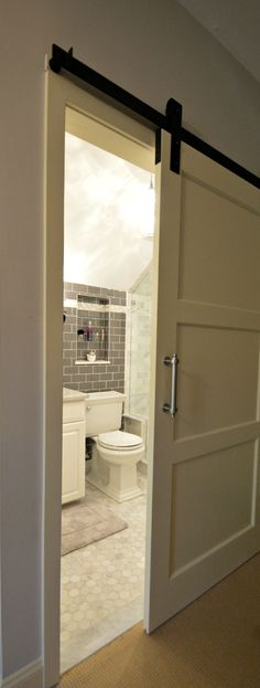 Tiny Bathroom Remodel features glass tile wall, carrara marble and custom recessed mirrored jewelry cabinet. We custom made this sliding barn door to take up less space in this tiny space. Design and build by Bryan Construction, Inc. & Bryan Cabinetry and Woodwork. A full service general contractor, builder and Custom Woodworking. www.BryanBuilds.com