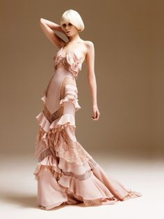 Versace - A lingerie evening dress in very light-weighted silk crepe and chiffon with embroidered chantilly lace, everything is in nude colour tonalities. A sequence of flounces and transparent strips with graphics wrap the entire body and give a '30s' revival effect to the dress.