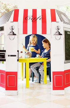 Photo of girls in cardboard playhouse cafe