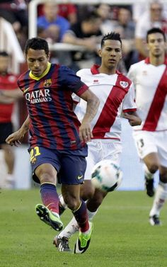 El defensa brasileño del FC Barcelona Adriano Correia controla el balón seguido por el centrocampista del Rayo Vallecano Jonathan Viera