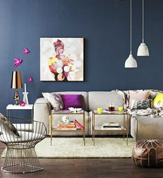 Grey couch, pops of colour in pillows, gold and glass tables