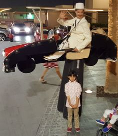 Here you can see the stiltwalker from Björn de Vils stilt theatre from germany at a performance in Dubai. This picture shows the stilt costume of a little red cabriolet which is able to devides itself in to two parts. The Walkacts are very popular Entertainment-Artists.