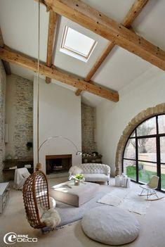 Grand salon sous une haute charpente en bois avec une décoration tout en blanc et de mobilier chiné et vintage