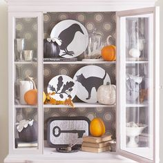 potential Halloween decorations: Scare up this spooky plate display in minutes with our free patterns. Print the crow, branch, cat, and skeleton key designs onto paper, then cut out. Trace onto the back side of self-adhesive vinyl or shelf liner. Trim and adhere the silhouettes to white plates or a tray.