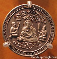 This appears to be a coin with the design of Guru Nanak Dev Ji
