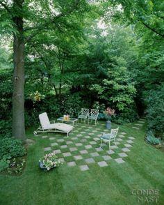 Dans cette cour verdoyante, l'idée d'un effet damier pour délimiter le coin repos est géniale.