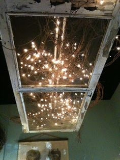 an old screen door hanging from a ceiling with lights and branches. So rustic and simple yet stunning.