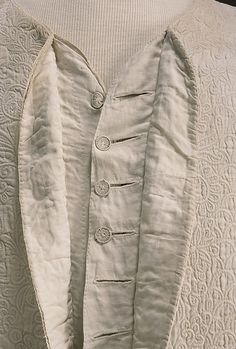 "Detail front closure, waistcoat, probably England, Plain weave bleached white linen, quilted to shape with intricately corded designs, ""French closure"" with wire and thread-work buttons, linen lining. Possibly jumps?"