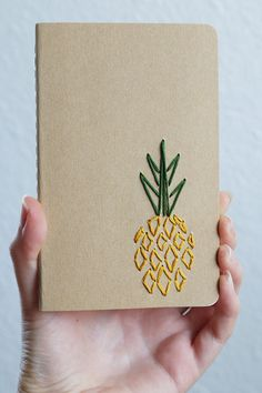 A pineapple is embroidered with mustard yellow and green threads on a lined kraft brown notebook, perfect for your summer plan making. Staying organized just became a bit more fun with this hand embroidered notebook. A perfect size to fit in your bag, ready to be filled with your sketches and lists.  Notebook: 3.5 x 5.5 inches Pages: 64  Find more here: https://www.etsy.com/shop/PoppyandFern?section_id=14287899