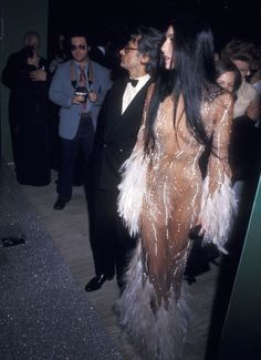 """Cher collaborated on many indelible looks with the designer Bob Mackie, but this is one that really got people talking — and wanting a copy for themselves. She first wore this feathery naked dress to the Metropolitan Museum in 1974, then again on the cover of TIME magazine in 1975. """"When Cher was on the cover of TIME, in her see-through dress, every tired old broad in Hollywood called asking me for one just like it,"""" Mackie said in 2014. Kim Kardashian paid homage to Cher's dress when she…"""