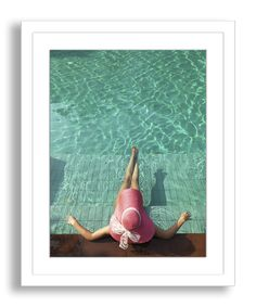 A woman kicks back poolside in this transporting image. Set off with a crisp white mat, the work comes beautifully framed in white wood molding.