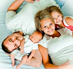 I like the idea of the baby right there and Mom laying across Dad. Super Cute. Could work even without the little girl.