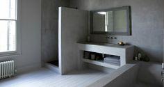 reforma baño con zona de ducha, mueble con lavabo y bañera de obra, acabado microcemento, parquet pintado blanco.