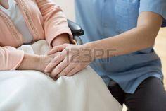 silla de ruedas: Enfermera de la mano de una mujer en una silla de ruedas Foto de archivo