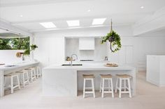 A beautiful white on white home renovation in North Sydney. Large L shape kitchen with island bench and three large sky lights.