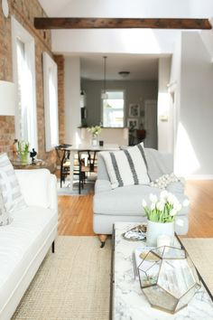 The Everygirl Co-founder Danielle Moss' Chicago Apartment Tour #theeverygirl || neutral interiors, white couch, jute rug, marble coffee table, exposed brick