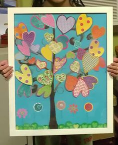 I saw a similar painting in a store and decided to have my daughter use leftover scrapbook  paper for the hearts. She painted the background and i drew the tree she punched out the grass and flowers. My kids names are written on the stem of the flower. She painted the frame.