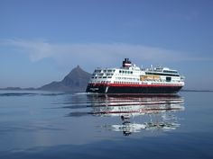 Hurtigruten ship M/S Trollfjord passing the island Hestmannen and the Arctic Circle.