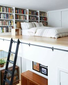 The small bedroom of a split level studio with built-in book shelves and wardrobe, brilliant space saver storage ideas.