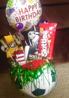 """My idea for my Boyfriends birthday! (who plays soccer) I cut a cheap soccer ball in half, put some styrofoam in the bottom, and put his favorite candies on skewers. I then tucked some shirts and gift cards in there. Lastly I added some """"grass"""" and voila!"""