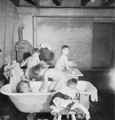 THE LIBERATION OF BERGEN-BELSEN CONCENTRATION CAMP, MAY 1945. Women and children bathing in the bath-house before being given clean clothes.