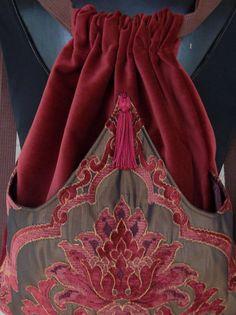 Mochila artesanal original hecho con terciopelo oscuro moho. El bolsillo exterior es de tonos de óxido a Borgoña e iridiscente marrón con arcos de tela de tapicería en el medio y cosido en el punto. Este bolsillo exterior está forrado con raso. La bolsa se está serged en el interior y mide 14 x 18.  La borla es Borgoña.  Esta mochila es genial con eso fuera de bolsillo para esconder su agua o libro. Resulta ideal para on the girls go.