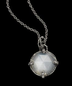 """SPELLBOUND  The """"Spellbound"""" pendant features a custom-cut, hand-carved 14 mm round faceted cabochon stone in a hand - textured setting and pave diamond claws. Shown in 18k blackened white gold, hand carved moonstone, with colorless and ice diamonds, 0.13 carat total  4,500 USD"""