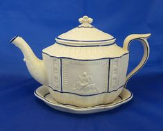 """Castleford Pottery Stoneware Teapot and Trivet Set  7"""" (17.7 cm) H (with trivet and lid) x 11"""" (28 cm) W  Condition: There is a small firing crack to one of the applied vignettes   piece is in excellent condition. Moulded no.17 on base teapot  £640  USA BIN N/S"""