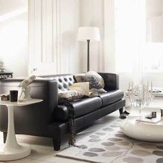 Feature a black sofa as a major contrast piece is an all-light room. This is a daring way to go, but it's striking, dramatic and makes the choice to go with a black sofa appear very intentional. Via Living Etc..