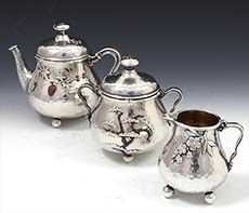 "A sterling hand hammered three piece tea set by Whiting with applied silver and copper motifs including berries, bugs, branches and leaves. All pieces have applied ball feet and handles, the teapot and sugar bowl with pull off lids. Height teapot 5 1/4"" to finial; sugar bowl 4 1/2"" and creamer 3 1/4""; combined weight 25.50 troy ounces. Marked with the Whiting logo, sterling and 439."