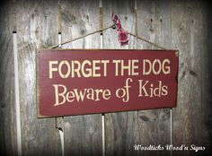 """This wood sign is made from pine, and measures Approx 5.5""""W x 13""""L. It reads """"Forget the Dog Beware of the Kids"""". The front is painted a barn red then distressed, the back is stained. We've used a pie"""