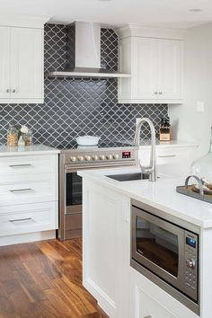Under-counter microwave is built into a white marble countertop center island surrounded by stainless steel appliances and accents.