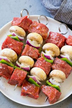 Skewers of beef, mushrooms, peppers and onions on a plate. beef steak Steak Kabobs with Garlic Butter - Dinner at the Zoo Beef Recipes, Cooking Recipes, Healthy Recipes, Grill Recipes, Steak Kabobs, Beef Skewers, Steak Kabob Marinade, Shrimp Kabobs, Kebabs On The Grill