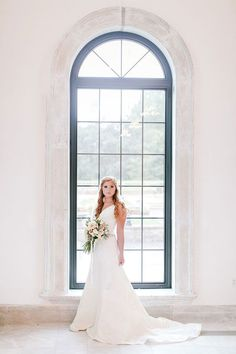 A classic wedding dress that's a dream to accessorize, this Oleg Cassini A-line gown features lace appliques and buttons all the way down the back. Exclusively at David's Bridal. Photo by Radion Photography.