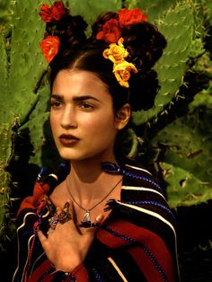 This photo inspired from Frida Kahlo is my fav. Love the flowers in her hair posed in front of a cactus. The rings & the native wrap.
