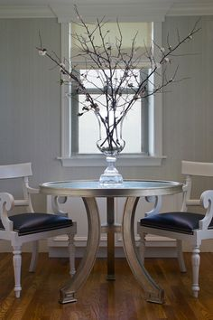 Chic dining room with gray textured walls, round silver Greek key table, white chairs with black leather cushions and Sakura.