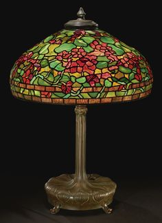 """Tiffany Studios """"NASTURTIUM"""" TABLE LAMP shade with small early tag impressed TIFFANY STUDIOS/NEW YORK telescopic base impressed TIFFANY STUDIOS/NEW YORK/28620 and with the Tiffany Glass & Decorating Company monogram leaded glass and patinated bronze 30 1/2 in. (77.5 cm) high 22 3/4 in. (57.8 cm) diameter of shade circa 1910"""