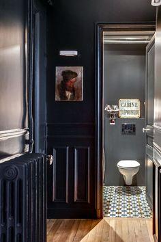 Toilette lookée dans le couloir bleu nuit. Le parquet jouxte des carreaux de ciment