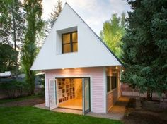 Small artist's studio inspired by the Victorian architecture of the surrounding historic homes. At 500 sq ft, the gable-roofed mini cottage provides space for an office, a library and a weaving area.