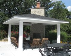 Poolside covered outdoor room in Chesterfield providing much needed shade and seating. The stone fireplace will extend the season well beyond pool season. The furniture is by Windward design.