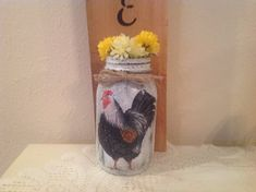 Hand decorated mason jar with rooster. Board left natural with black stenciled HOME . Jar is white spattered and distressed in black. Hangs on