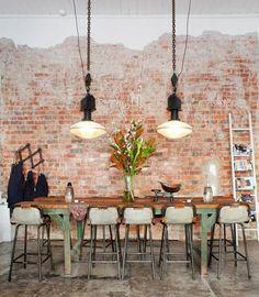 Esta parede em degradê rouba a cena na sala de jantar, que ainda possui piso em cimento queimado e uma mesa alta com banquetas.