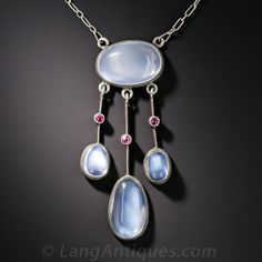 Silver Moonstone and Ruby Necklace. A lustrous quartet of lunar rocks (aka moonstones) exude a celestial sheen in this very lovely, early-twentieth century lavaliere necklace, hand crafted in silver and punctuated with small bezel-set rubies. The pendant measures 1 and 3/16 inches, the chain measures 16 inches.