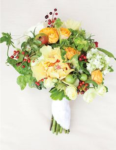 """Garden Variety"" bouquet with geranium leaves, june berries, oak leaf hydrangea, green beans, unripened tomatoes, mini pears, yellow peonies, spray garden roses, and passion vine 
