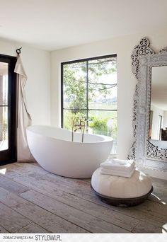 .beautiful bedroom, large mirror, free standing bath tub, white painted floor boards